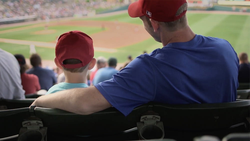 Father and son watchin professional baseball game in stands